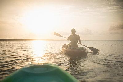 Caucasian woman rowing canoe on still lake - p555m1411116 by John Fedele