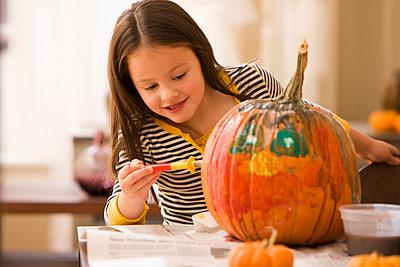 Caucasian girl decorating pumpkin - p555m1479012 by KidStock