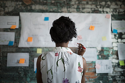Creative businesswoman brainstorming, reviewing flow chart hanging on brick wall in office - p1192m1447548 by Hero Images