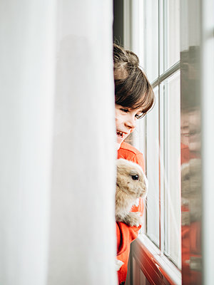 Little girl holding rabbit by the window - p1522m2176538 by Almag