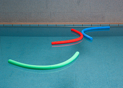 Aqua noodles floating on water of indoor swimming pool - p300m1115011f by Wolfgang Weinhäupl