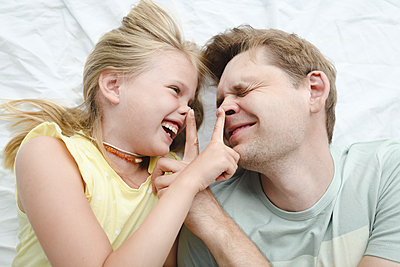 Father happy smiling daughter in bed - p300m2274385 by Ekaterina Yakunina