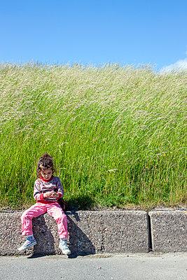 Mädchen sitzt am Deich - p754m1590122 von Valea Diller-El Khazrajy