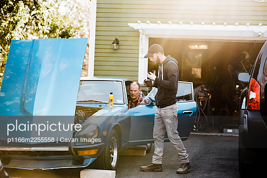 millennial man and father in law working on old classic car together - p1166m2255558 by Cavan Images