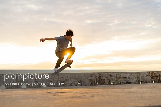 Young Chinese man skateboarding at sunsrise near the beach - p300m2012287 von VITTA GALLERY