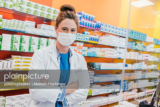 Fermale pharmacist with surgical mask standing in chemist shop - p300m2243841 by Mareen Fischinger