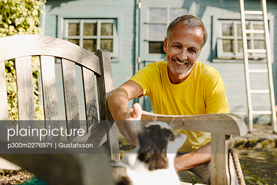 Smiling man stroking cat on armchair in back yard - p300m2276971 by Gustafsson