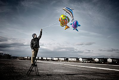 Holding balloons in the grey sky - p1007m1020632 by Tilby Vattard