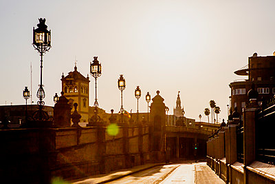 Looking down an empty sun drenched street with a bridge in the city of Seville in Spain - p1057m2164318 by Stephen Shepherd