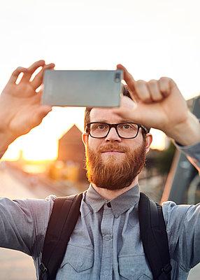 Mann fotografiert mit Smartphone - p1124m1169974 von Willing-Holtz