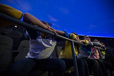 Students in 3D glasses enjoying planetarium show - p1192m1019868f by Hero Images