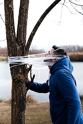 Man tied to a tree with wool - p1521m2157602 by Charlotte Zobel