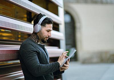 Handsome man with headphones using digital tablet against metal wall - p300m2252106 by Jose Carlos Ichiro
