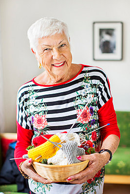 Portrait of happy senior woman holding knitting basket at nursing home - p426m977479f by Maskot