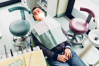 Male patient in dentist chair, elevated view - p429m1561691 by Eugenio Marongiu