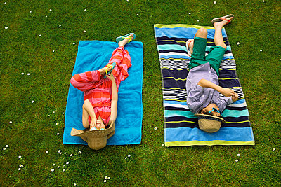 Boy and Girl Sunbathing on Lawn - p669m927477 by Jutta Klee photography