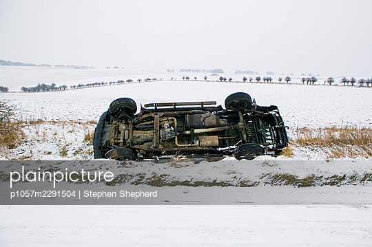 A large car laying in a ditch where it has skidded off of an icy and snow laden road. The vehicle has rolled over on it's side with roof in the ditch on a country lane in the middle of winter with snow fileds and roads all around. - p1057m2291504 by Stephen Shepherd