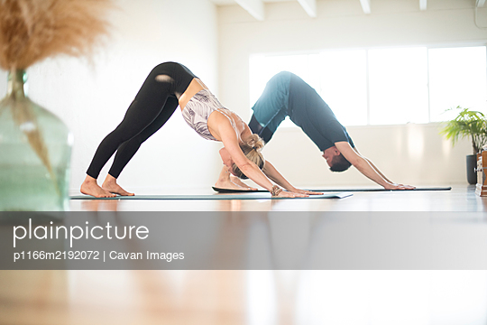 A couple in Downward Facing Dog position during yoga. - p1166m2192072 by Cavan Images
