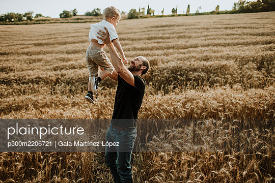Father spending leisure time with son in wheat farm - p300m2206721 by Gala Martínez López