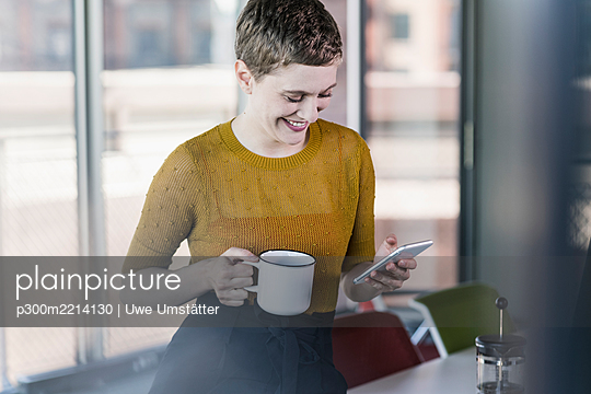 Smiling businesswoman in office holding coffee mug and mobile phone - p300m2214130 by Uwe Umstätter