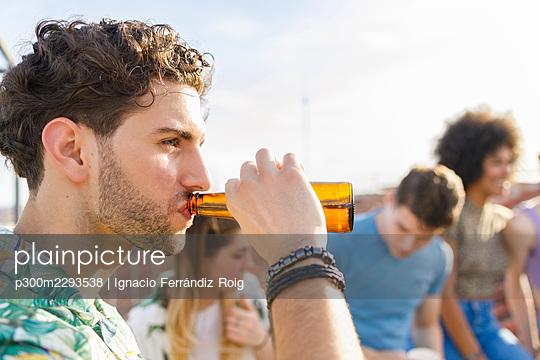 Young man drinking beer during party - p300m2293538 by Ignacio Ferrándiz Roig
