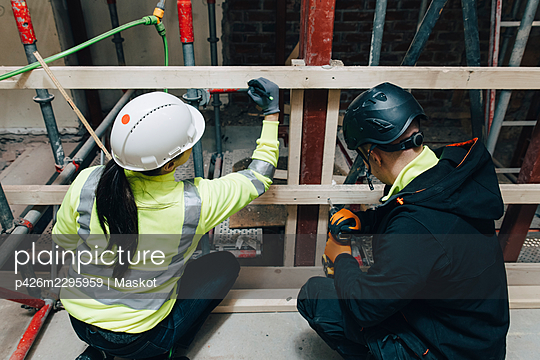 Male and female colleagues working together at construction site - p426m2295959 by Maskot