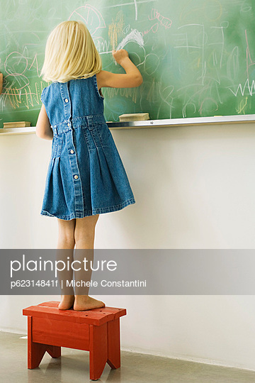 Little girl standing on stool, scribbling on blackboard, rear view - p62314841f by Michele Constantini