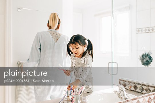 Girl with mother selecting toothbrush in bathroom - p924m2091361 by Sara Monika