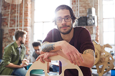 Portrait confident male designer with tattoos leaning on prototype in workshop - p1023m1486399 by Agnieszka Olek