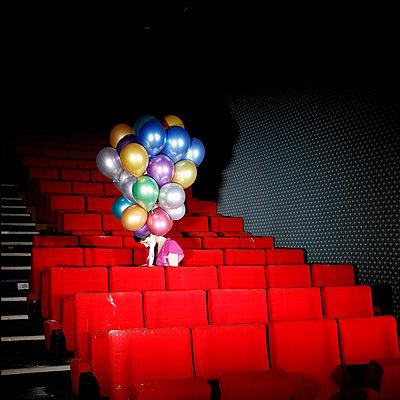 Frau mit bunten Luftballons in einem alten Kinosaal - p1105m2254511 von Virginie Plauchut