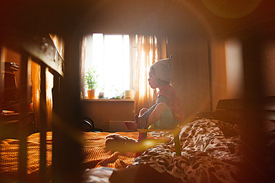 Child in the evening light in the bedroom - p1642m2216183 by V-fokuse