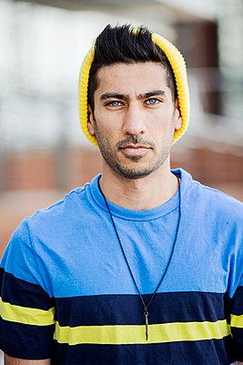Portrait of fashionable young man wearing cap an striped t-shirt - p300m2005579 von Jan Tepass