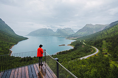 Norway, Senja island, rear view of man standing on an observation deck at the coast - p300m2042284 by Kike Arnaiz