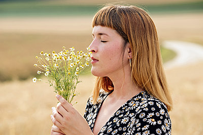 Young woman with eyes closed smelling bunch of chamomile flower - p300m2131856 by FL photography