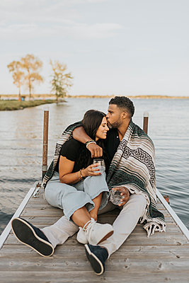 Man kissing woman while sitting on pier against lake - p300m2227152 by Sara Monika