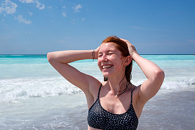 Cheerful young woman standing with hand in hair at beach during sunny day - p300m2256119 by Lisa und Wilfried Bahnmüller
