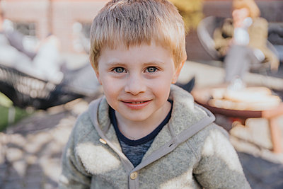 Cute boy smiling while standing in backyard - p300m2286258 by Mareen Fischinger