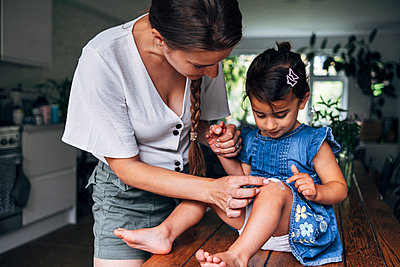 Mother holding hand while putting bandage on daughter's knee at home - p300m2293291 by Angel Santana Garcia