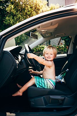 Side view of boy sitting in car pretending to drive, looking at camera smiling, Luino, Lombardy, Italy - p429m1105739 by JFCreatives