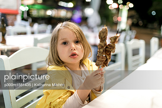 Greece, portrait of little girl sitting in a restaurant with two Souvlaki meat skewers - p300m1581435 von Katharina Mikhrin