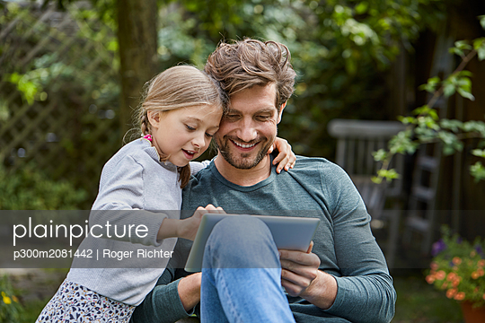 Happy father and daughter using tablet together in garden - p300m2081442 by Roger Richter