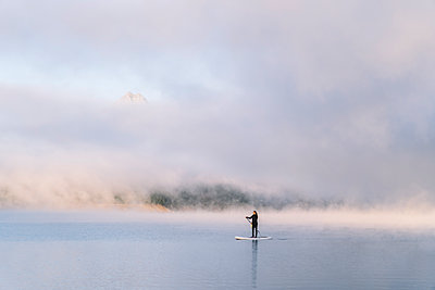 Woman stand up paddle surfing on a lake - p300m2170519 by Daniel González