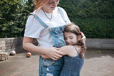 Daughter hugging mother on basketball court at back yard - p300m2214020 by Ekaterina Yakunina