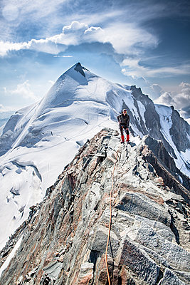 Mountaineer stands on mountain ridge - p327m1216697 by René Reichelt