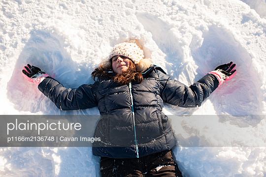 Overhead view of tween girl making snow angel in the front yard - p1166m2136748 by Cavan Images