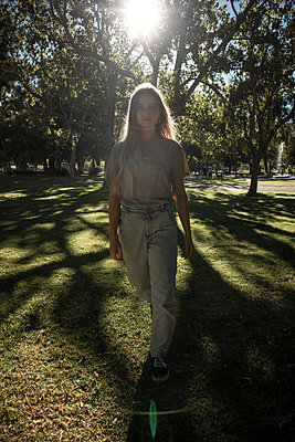 Teenage girl takes a walk in the park - p1640m2258519 by Holly & John
