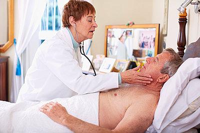 Doctor examining senior man at home - p300m978815f by zerocreatives