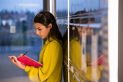 Woman writing in notepad at office - p429m1557632 by suedhang photography