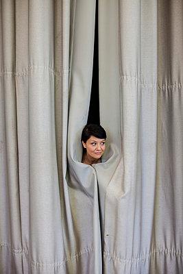 Junge Frau steckt ihren Kopf durch den Bühnenvorhang - p586m939396 von Kniel Synnatzschke
