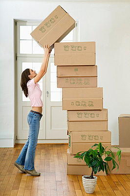 Woman stacking cardboard boxes - p6090357f by DRESDEN photography